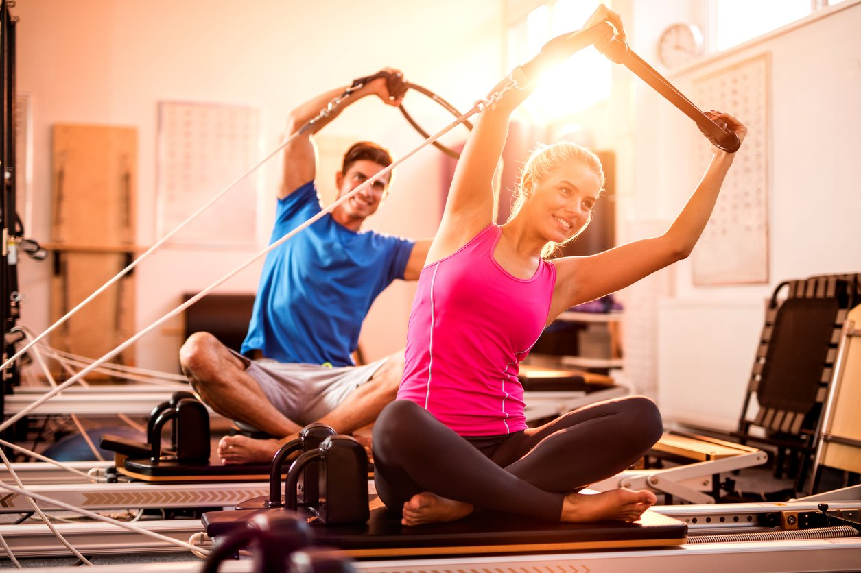 Pilates One homepage banner young couple doing Pilates on reformers